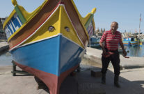 Fisherman painting his boat in Marsaslox on Malta
